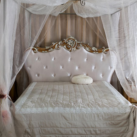 Voiles draped over four poster metal bed frame to make a canopy