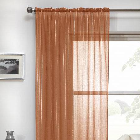 Copper voile panels hung on a metal pole at a window