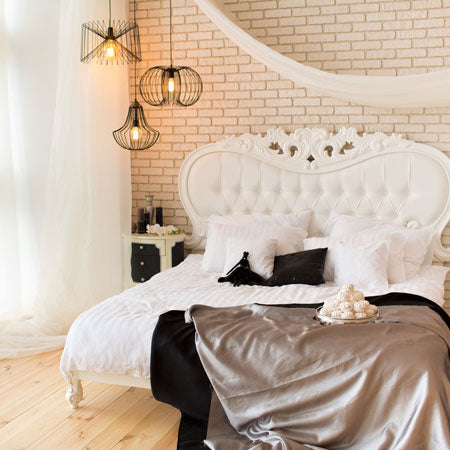 Ornate cream wood bed frame with voiles at the window and draped over the bed