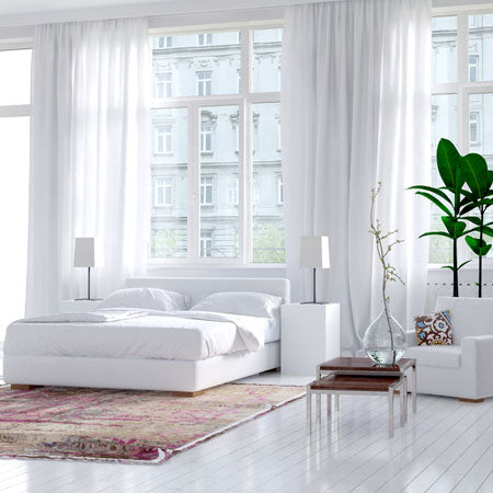 Large bedroom with glossy white wooden floors, white bedding and white voile panels in the windows