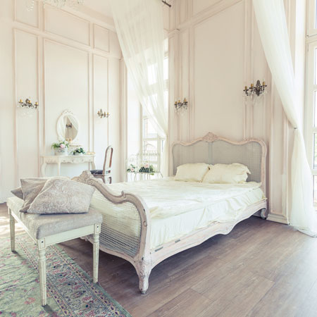 Large cream bedroom with wooden laminate flooring and double bed on wooden ornate bed frame
