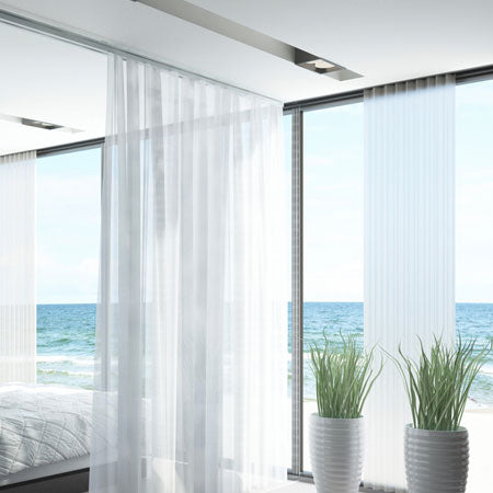 White voile panels at a luxury beach front apartment, with floor to ceiling windows looking out at the beach