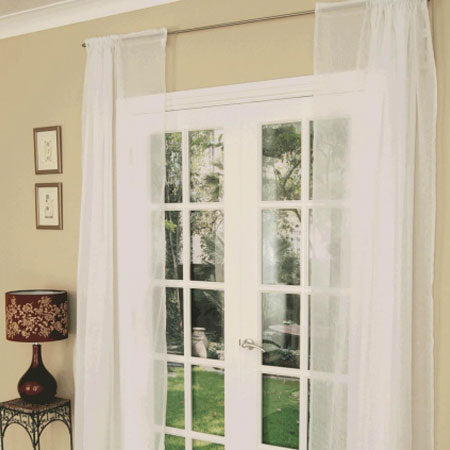White voile panels hung above french doors that open out to the garden