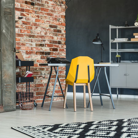 Modern livign space with exposed brick and one black wall, and yellow chair at a desk