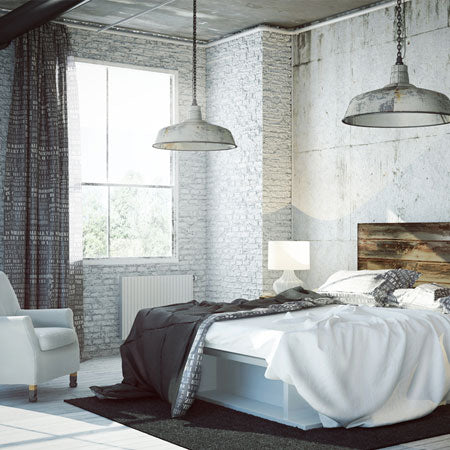 Industrial style bedroom with two distressed metal lampshades above a double bed