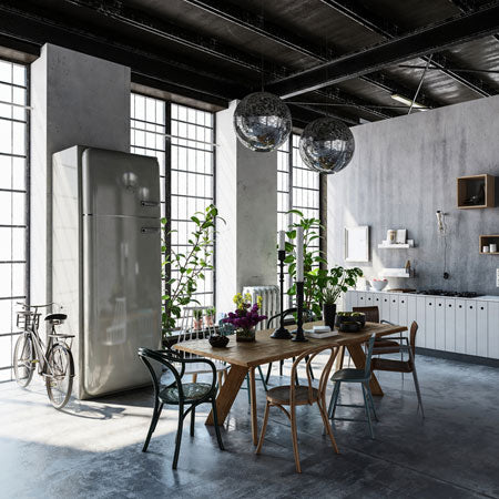 Industrial style dining room and kitchen with exposed ceiling joists and concrete surfaces