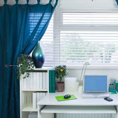 Teal voile curtains at a home office window, that also has white venetian blinds