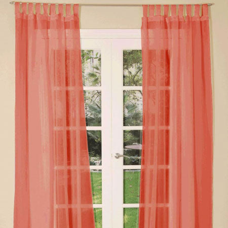 Red voile curtains at french garden doors in a living room