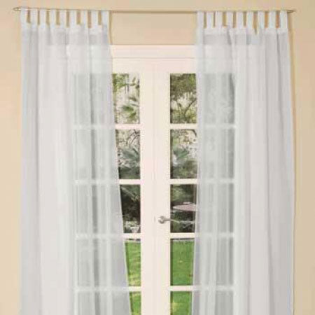 White voile curtains at a living room french door opening out to a garden