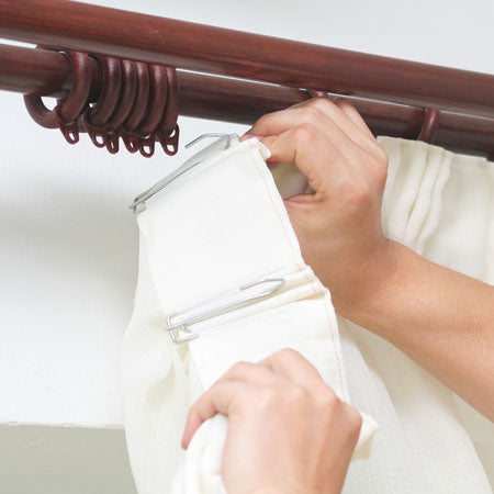 A pair of cream curtains being hung on a dark wooden curtain pole