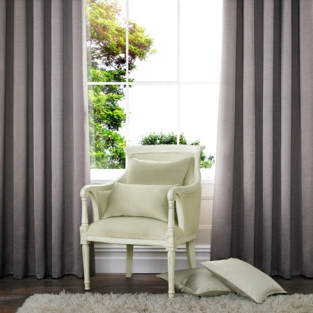 Grey made to measure curtains at a window, with a wooden cream armchair in the middle of the window