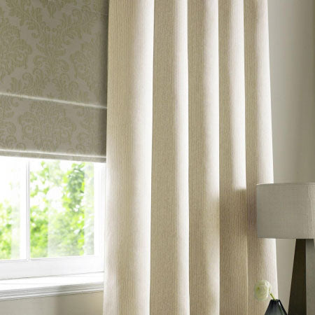 Cream made to measure curtains and grey roman blind at a living room window