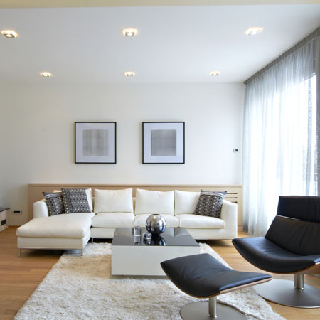 A bright white living room with white voiles at floor to ceiling windows