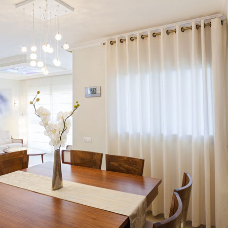 Cream eyelet voiles at a window in a dining room
