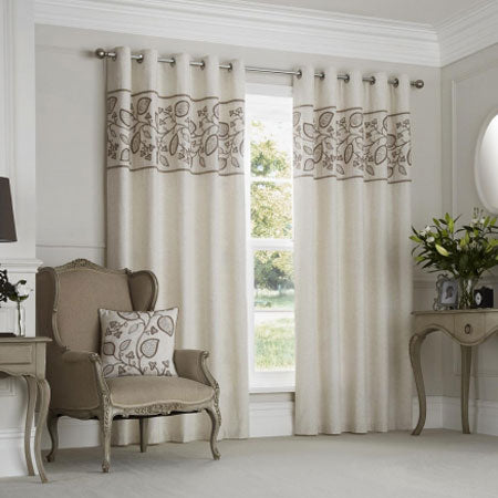 Cream and brown eyelet curtains with a brown patterned strip at across the top of the curtains