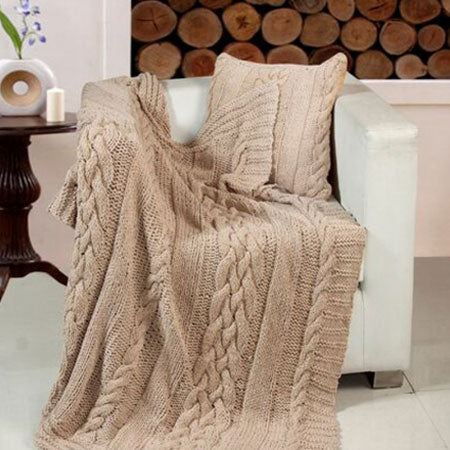 Brown knitted throw draped over a white leather armchair
