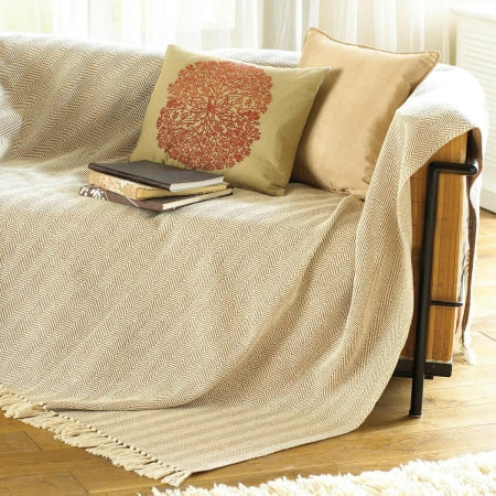 Beige throw draped over a sofa with matching cushions