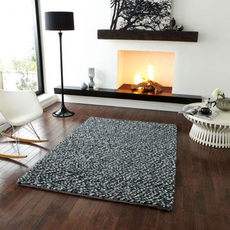 Grey speckled rug on dark wooden flooring