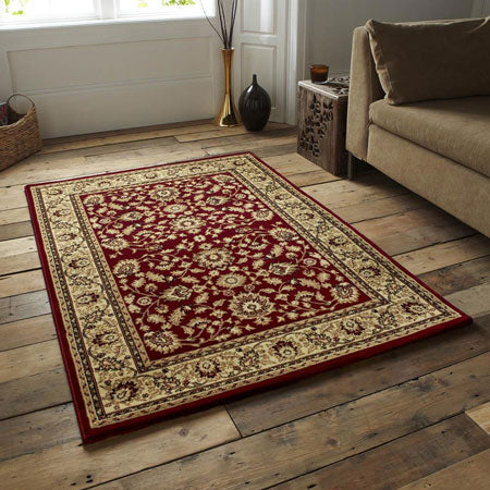Traditional patterned red and gold rectangular rug on wooden flooring