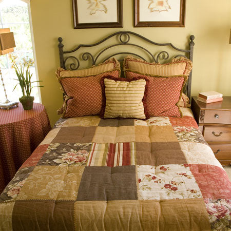 Brown, beige, red and cream patchwork bedding on a metal frame bed