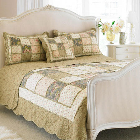 Green, cream and pink patchwork floral bedding on a white bed