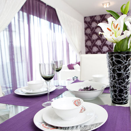 Purple Placemats And Purple Voiles In A White Dining Room