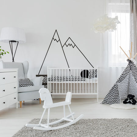 White nursery bedroom with black mountain outline decal on the wall, and black and white tepee tent in the corner