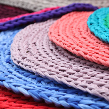 Round woven rugs in red, blue and purple piled on top of each other