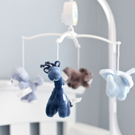 Light grey nursery with soft toy animal mobile over the cot