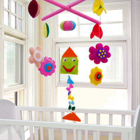 A white and cream nursery with cot by two windows in the corner of the room and a bright felt mobile with flowers and characters