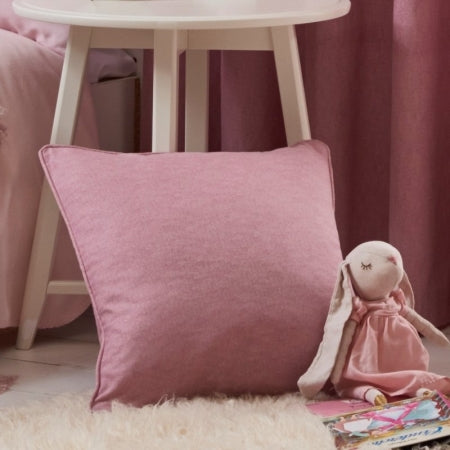 Blush pink square cushion leaning against a wooden stool