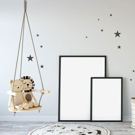 Soft toy lion and lioness on an indoor seat swing, in a light grey room with dark star decals on the wall