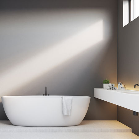 White curved bathtub and long white sink in a light beige bathroom