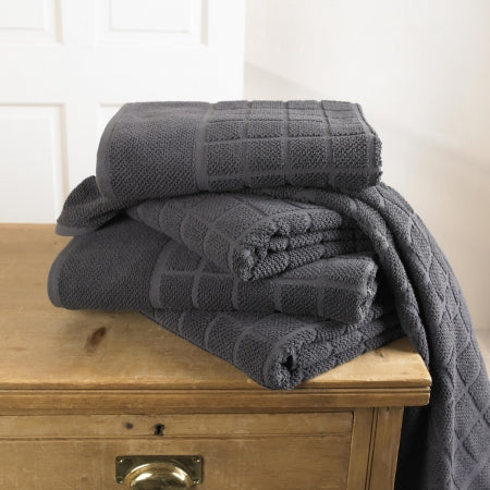 Stack of black towels on a oak set of drawers