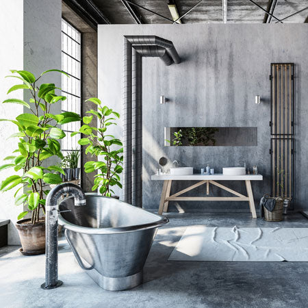 Industrial style bathroom with exposed beams and concrete surfaces, plus metal bathtub