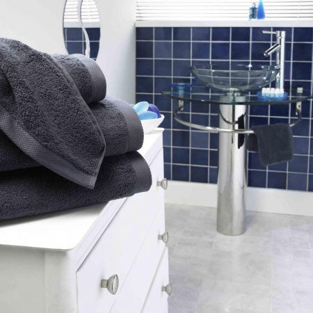 Black towel on white drawers in a modern bathroom, with dark blue tiles