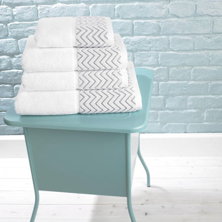 White towels on a mint green side table in a white and mint coloured bathroom