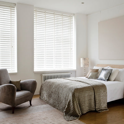 Two windows in a white bedroom with white venetian blinds
