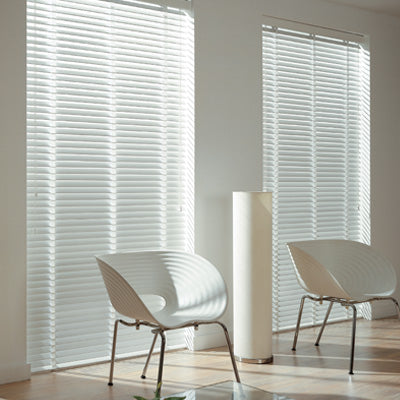 Two windows in a white room with white venetian blinds