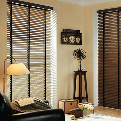 Warm natural cream living room with dark wooden venetian blinds and a black leather armchair