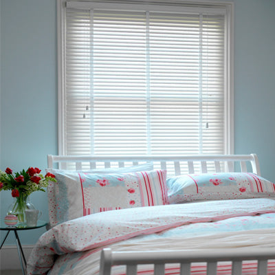 White venetian blinds in a light blue bedroom