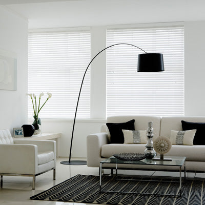 Two windows in a white living room, each with white venetian blinds