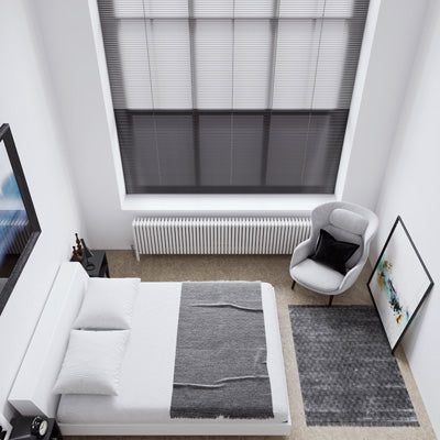 Looking down on a double bed from a height, with black venetian blinds in the very tall window