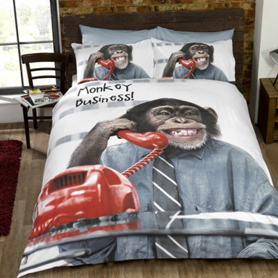 Double bedding with a chimpanzee wearing a shirt and tie, holding a red phone