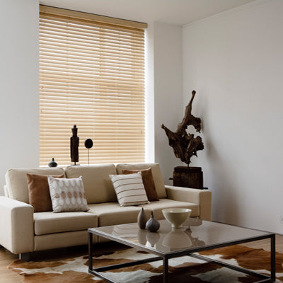 Light wooden venetian blinds in a white living room, with cream sofa