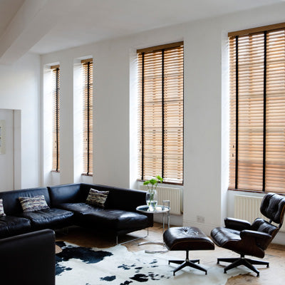 Wooden venetian blinds in four windows along a flat white wall, with black corner sofa in the room