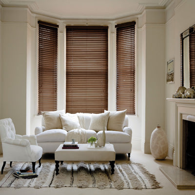 Dark wooden venetian blinds in a bay window, with cream sofa and white arm chair in a cream room
