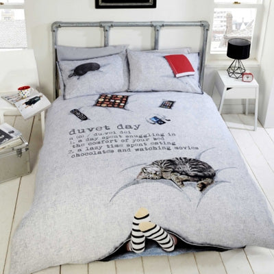 Light grey bedding, with a printed photo design of a cat on the bed, books, remote, and feet sticking out under the covers