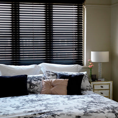 Black venetian blinds behind a double bed in a cream room