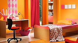 An orange bedroom with desk